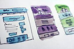 Rough sketch of web layouts in blue, purple, and green